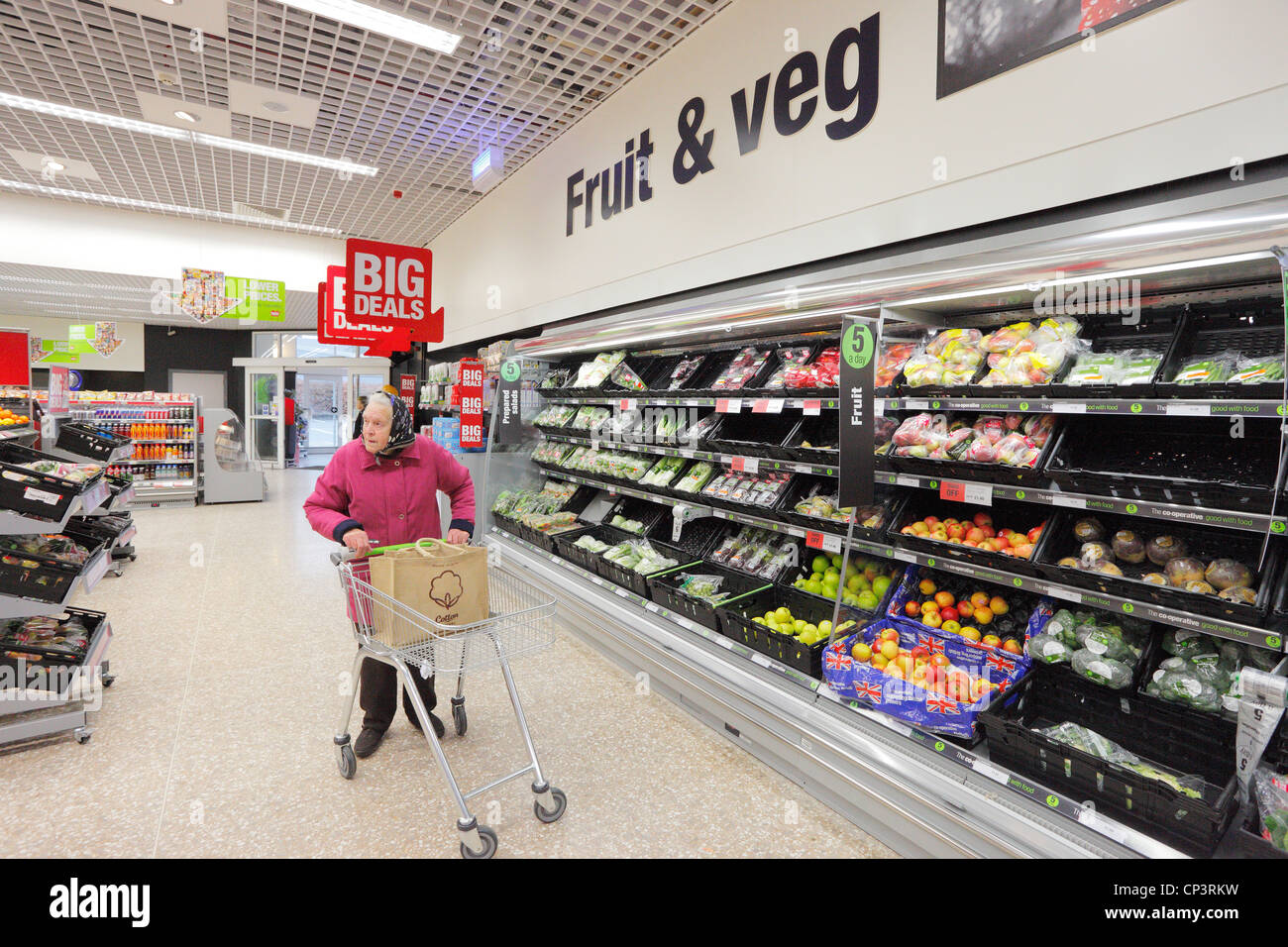 Old woman shopping pushing a trolley in a supermarket. Fruit and vegetable aisle. - Stock Image