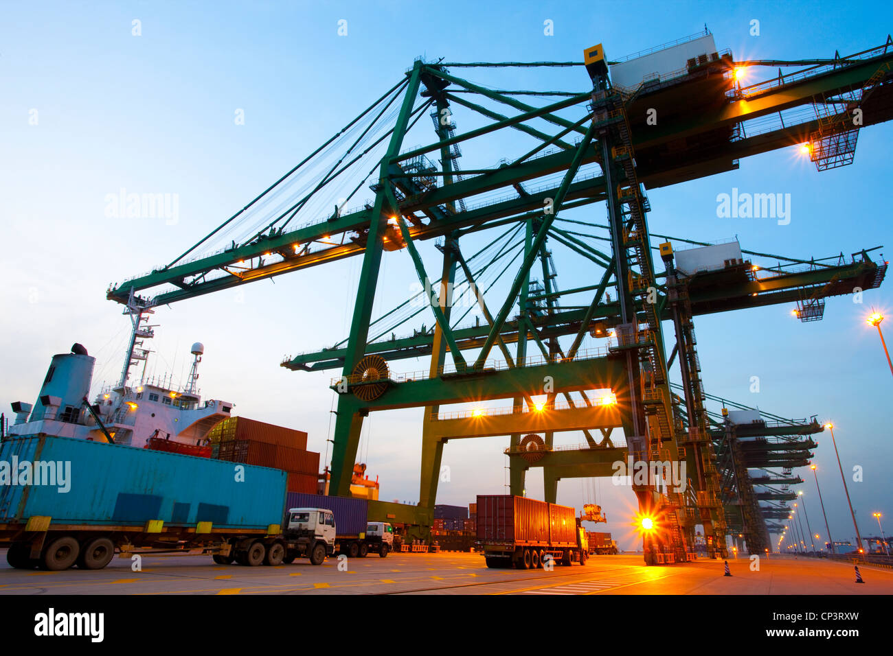 Cranes, cargo containers and trucks at a shipping port during dusk - Stock Image