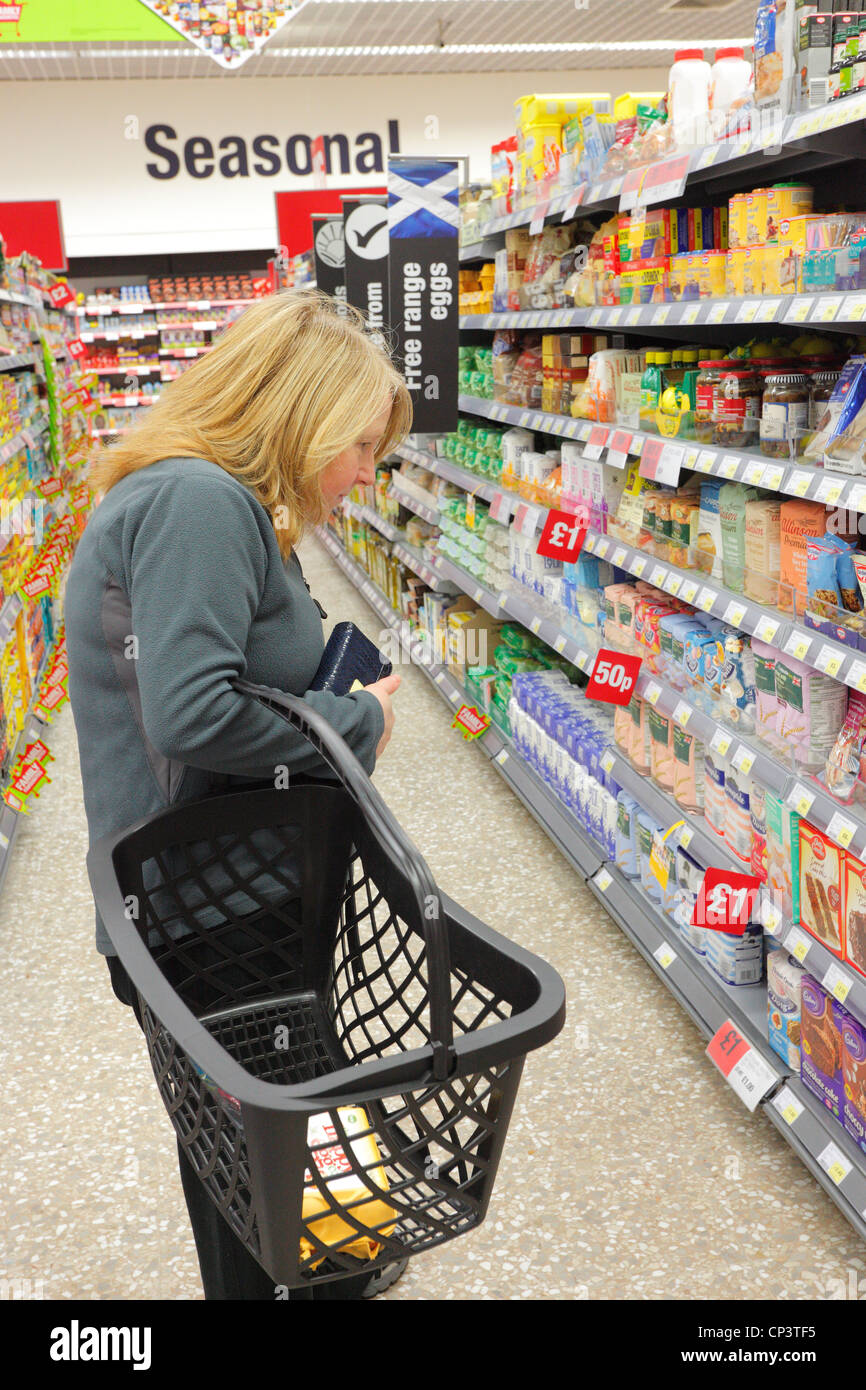 Woman with a basket shopping in a supermarket baking aisle. - Stock Image