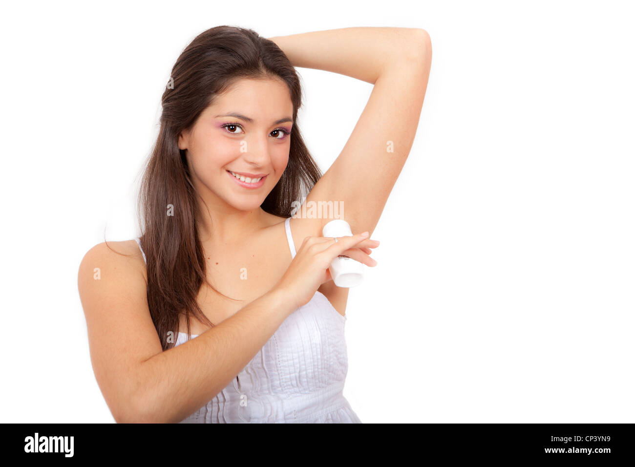 young woman putting on deodorant - Stock Image