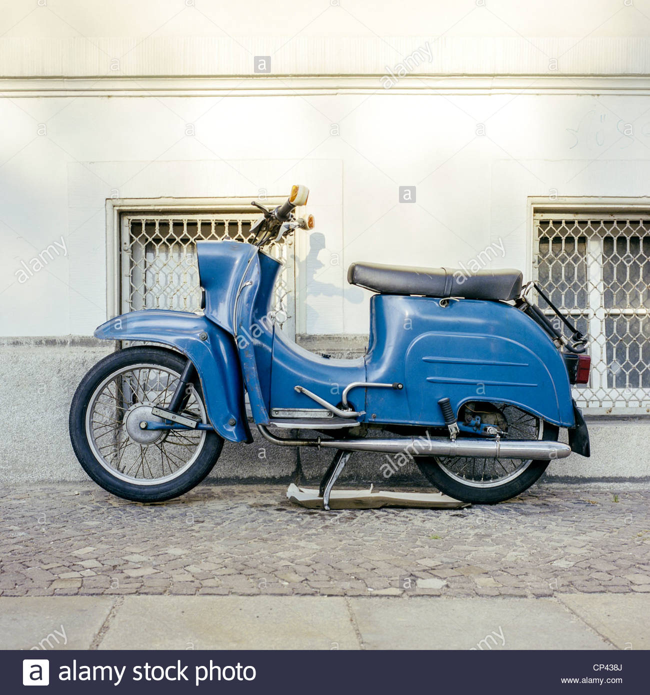 A Blue Vespa motorcyle parked on the sidewalk in Leipzig, Saxony, Germany - Stock Image