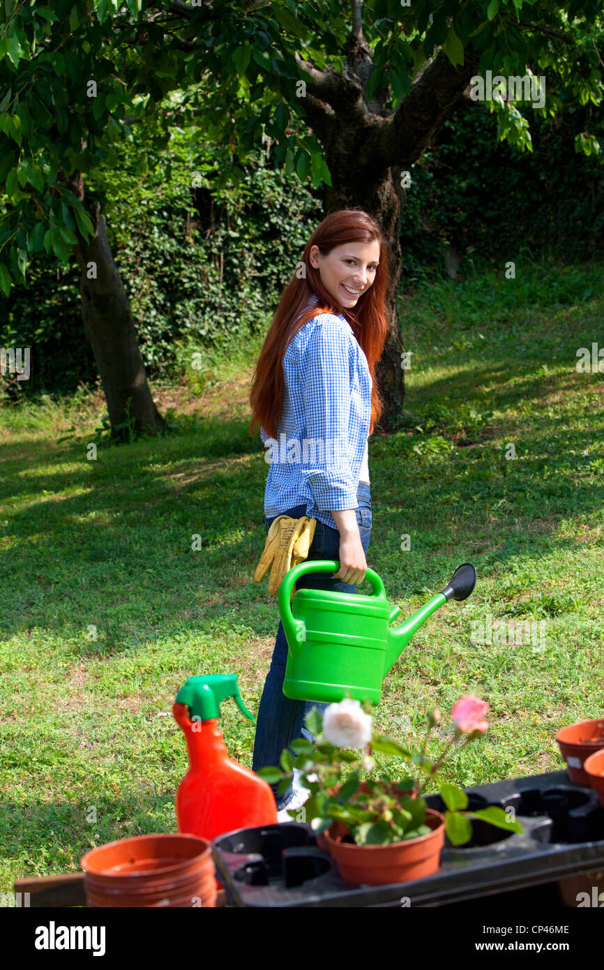 a woman with a watering can in garden - Stock Image