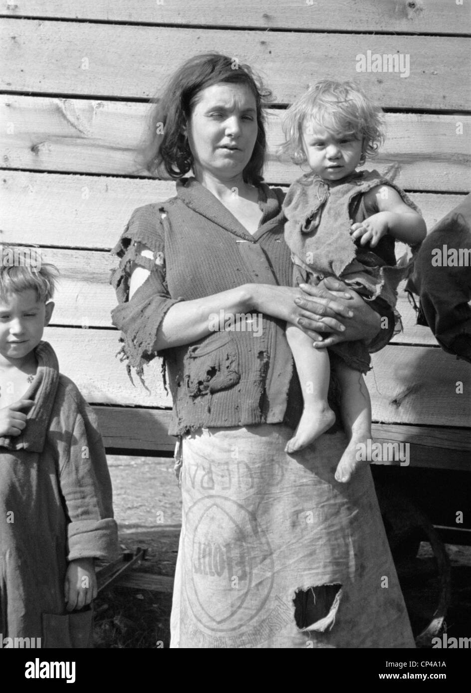 Young mother dressed in a ragged sweater and a skirt made of flour sacks holds her toddler. She lives with eight - Stock Image