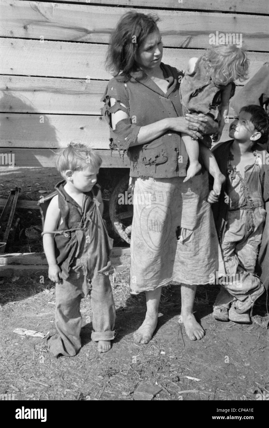 Young mother dressed in a ragged sweater and a skirt made of flour with three children also dressed in rags. She - Stock Image