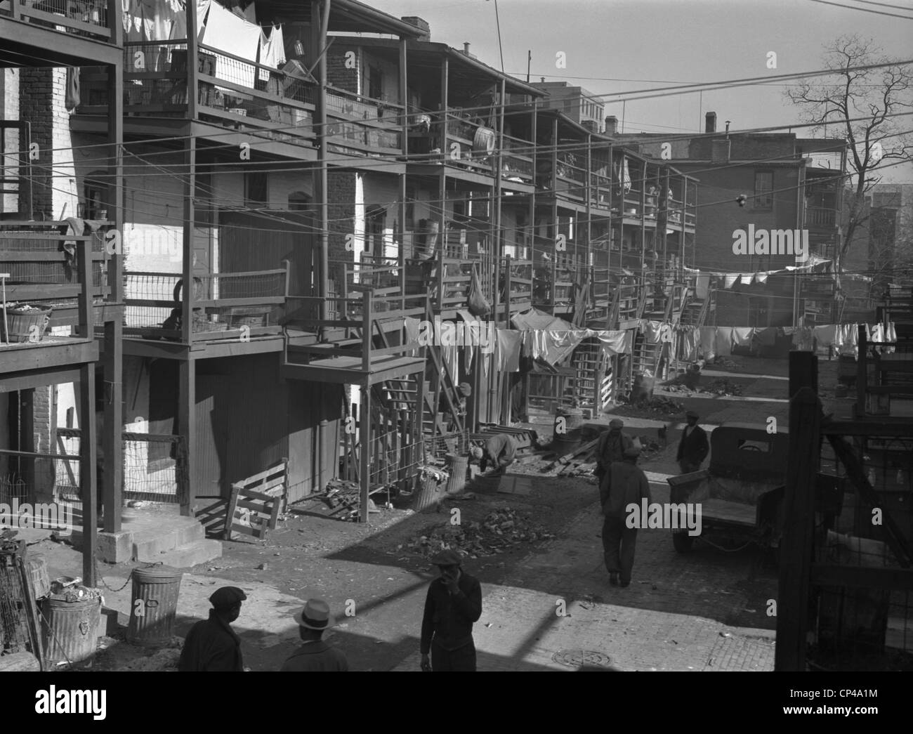 Depression era slums in Washington D.C. African American men in the backyards of three story row houses. Nov. 1935. - Stock Image