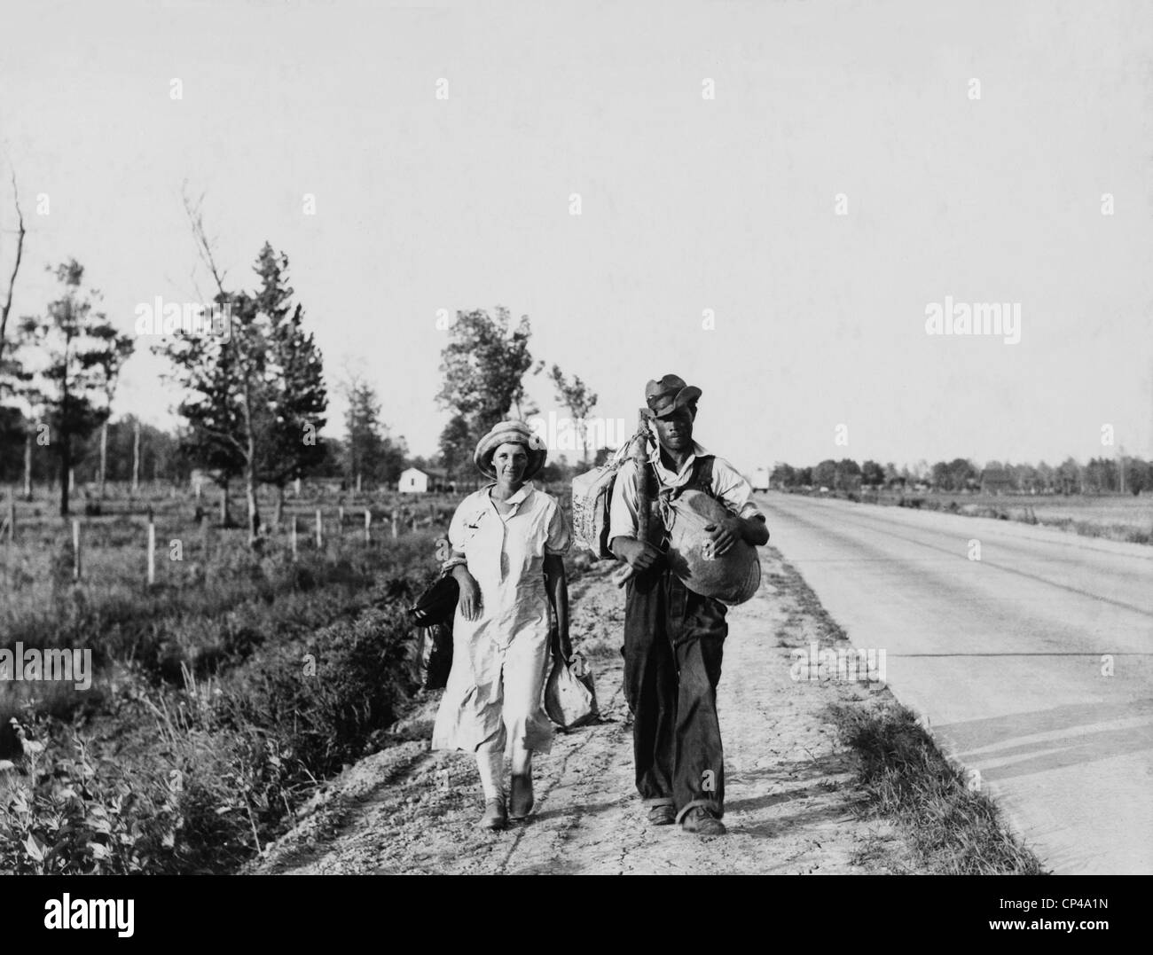'Oakies' couple migrating. Cotton workers on the road carrying all they possess as they say 'Damned - Stock Image