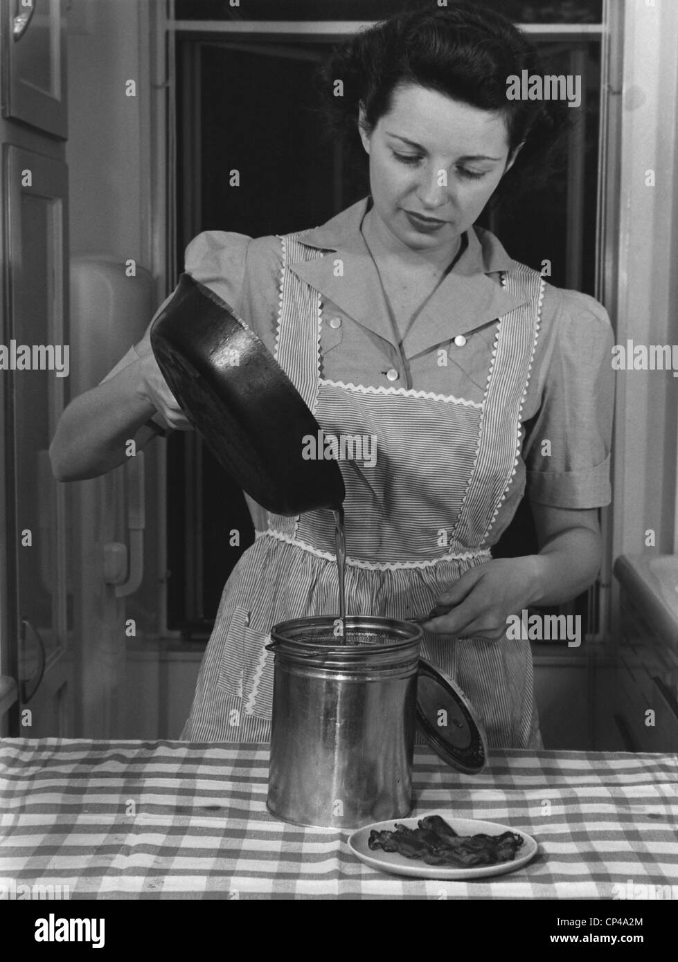 Housewife pouring waste fats that will be processed into ammunition for America's World War 2 military. - Stock Image
