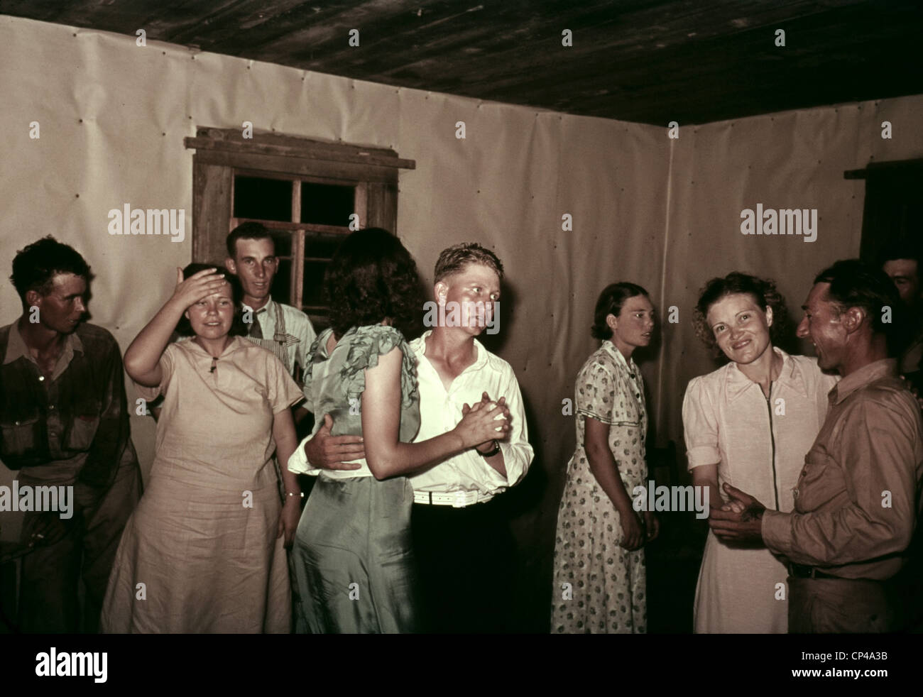 Square dance in rural home in McIntosh County Oklahoma. They dance in a simple interior with butcher paper covered - Stock Image