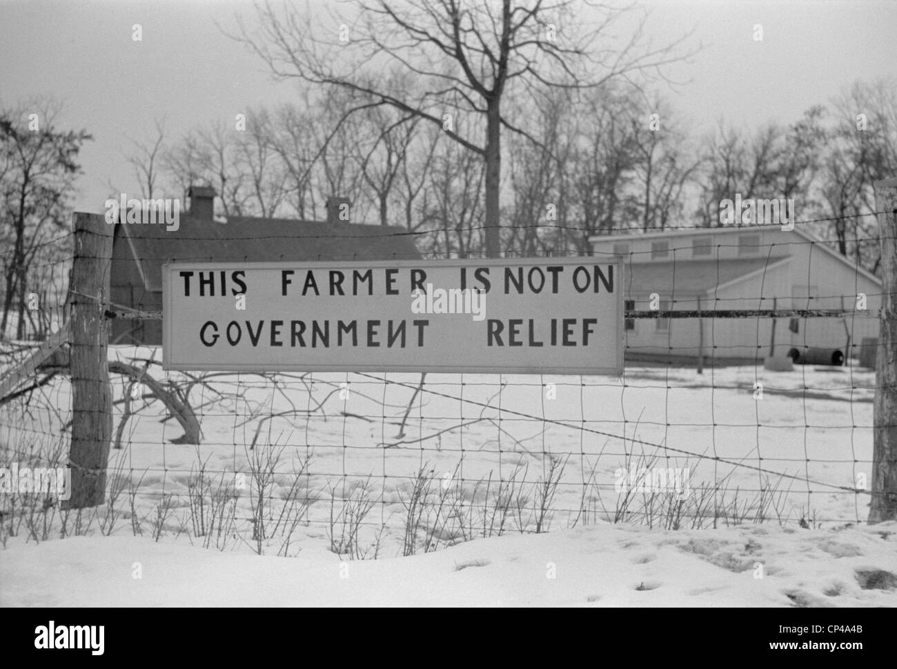 'This Farmer is not on Welfare ' reads a sign a wire fence. Iowa or Illinois Dec. 1940. - Stock Image