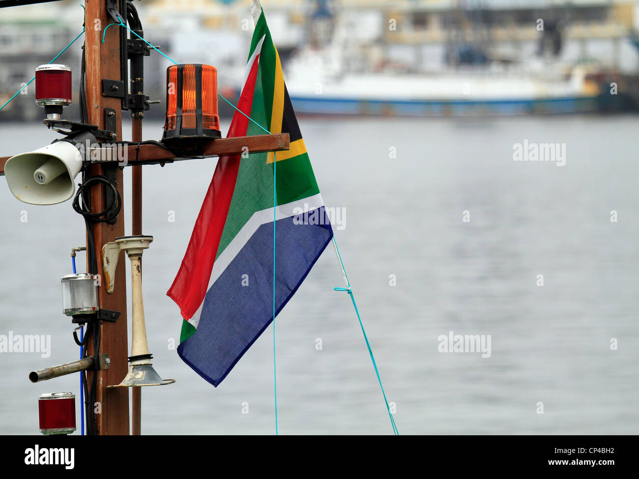 Mast on boat moored at the V&A Waterfront in Cape Town with fog horn, navigation light and a South African flag - Stock Image