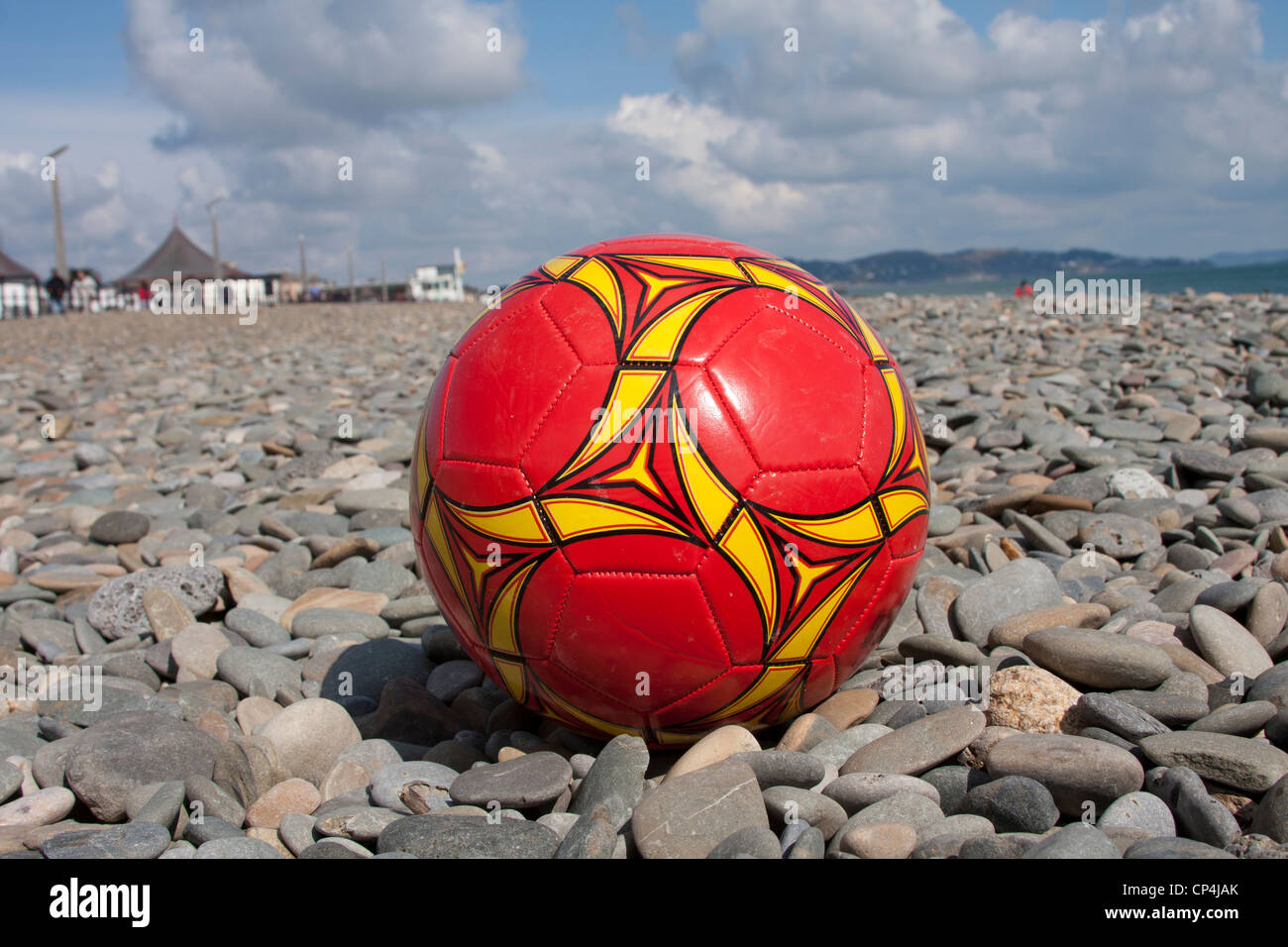 A football on a stony beach - Stock Image