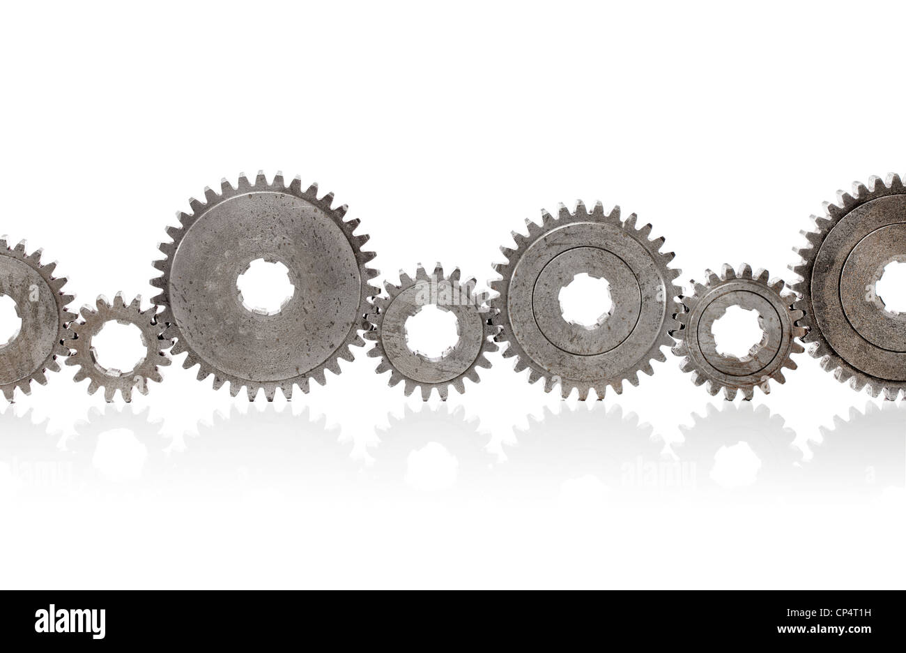 Old metallic cog gears arranged in a row. - Stock Image