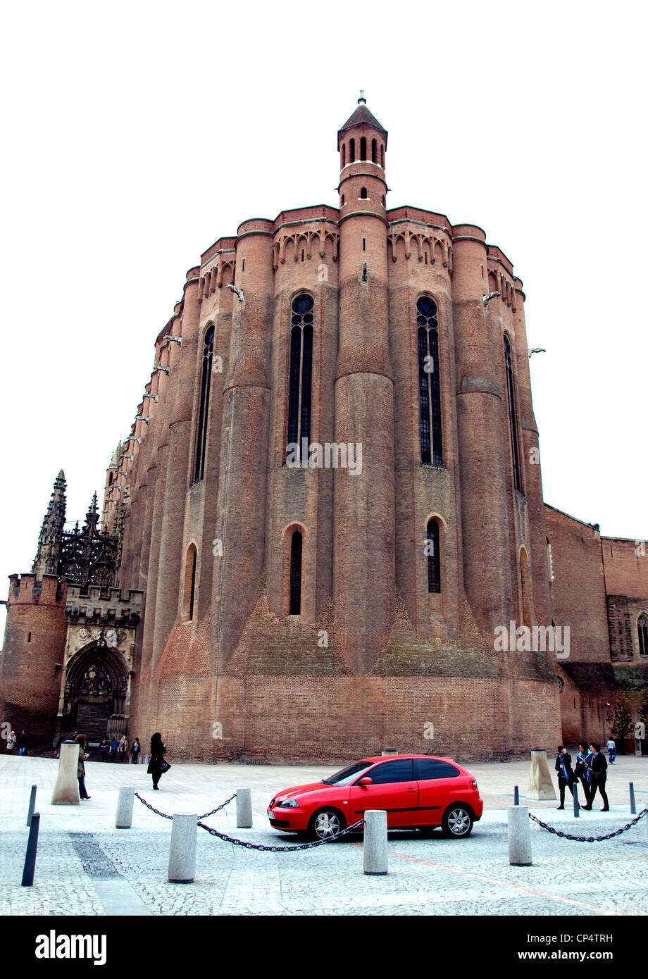 In medieval Albi, France, a small red car drives behind the city's vast brick cathedral providing captivating - Stock Image