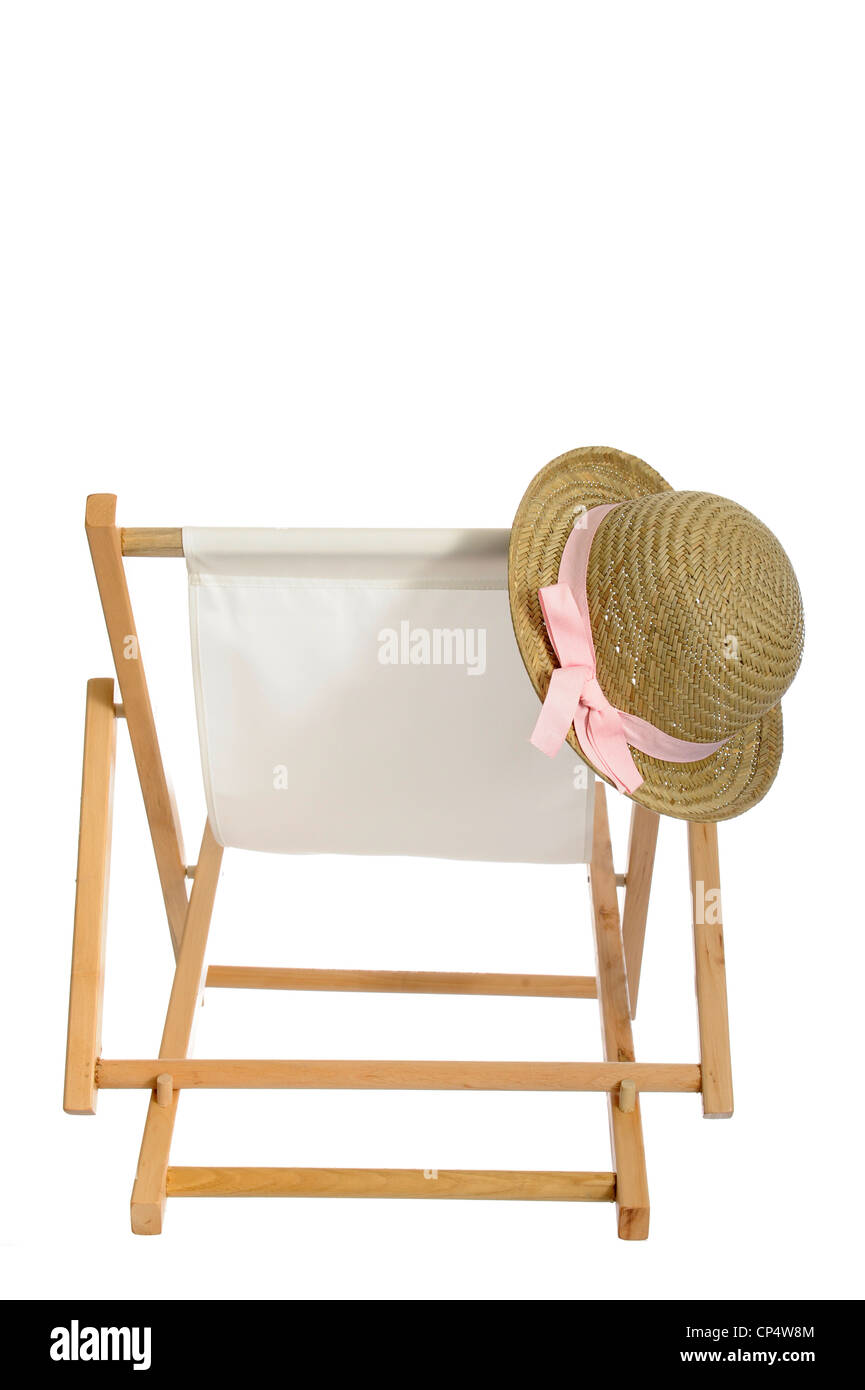 summer straw hat hanging on a deck chair. Isolated on white background - Stock Image