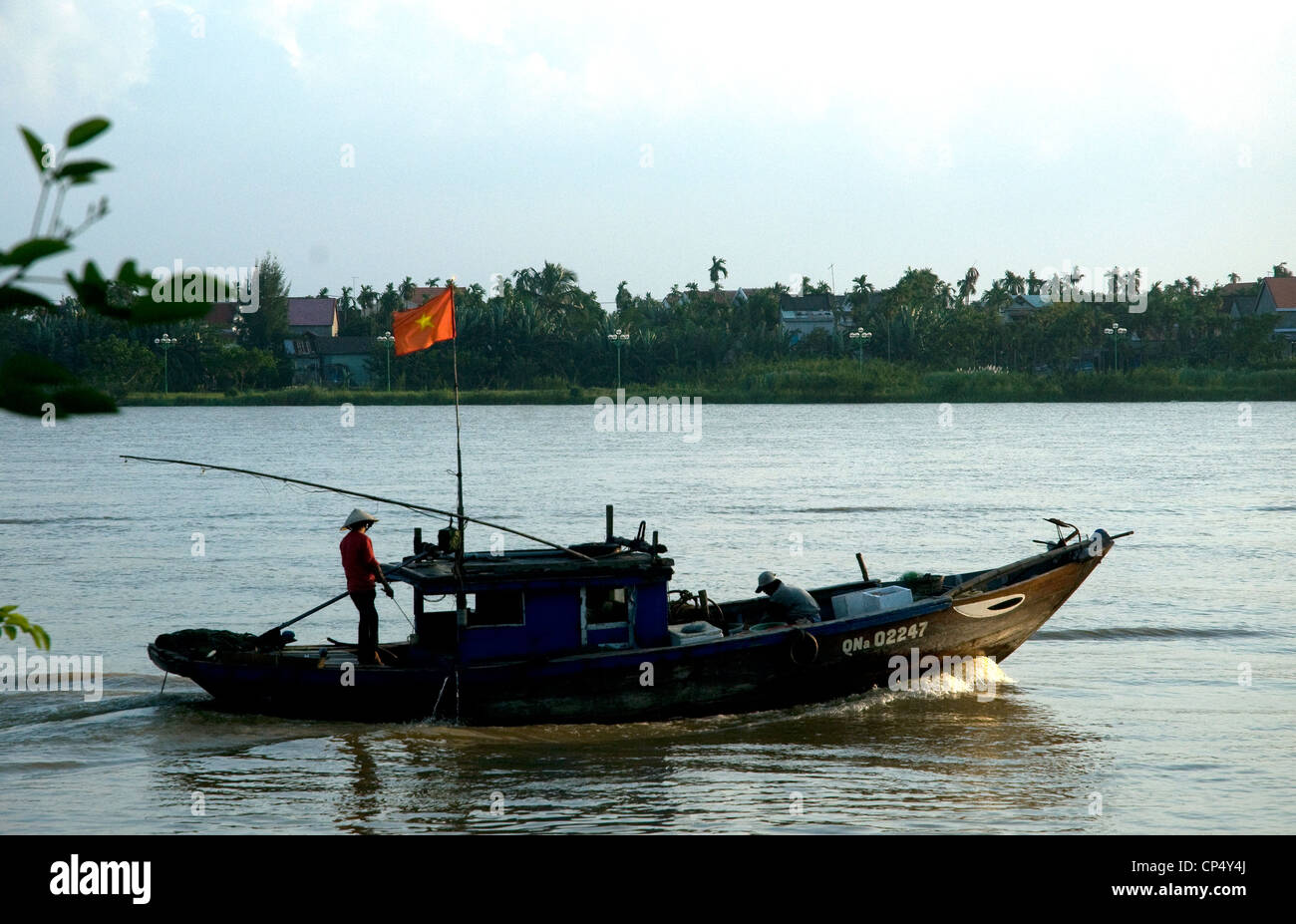 At dusk in Vietnam's Hoi An a single fishing boat returns to port - Stock Image