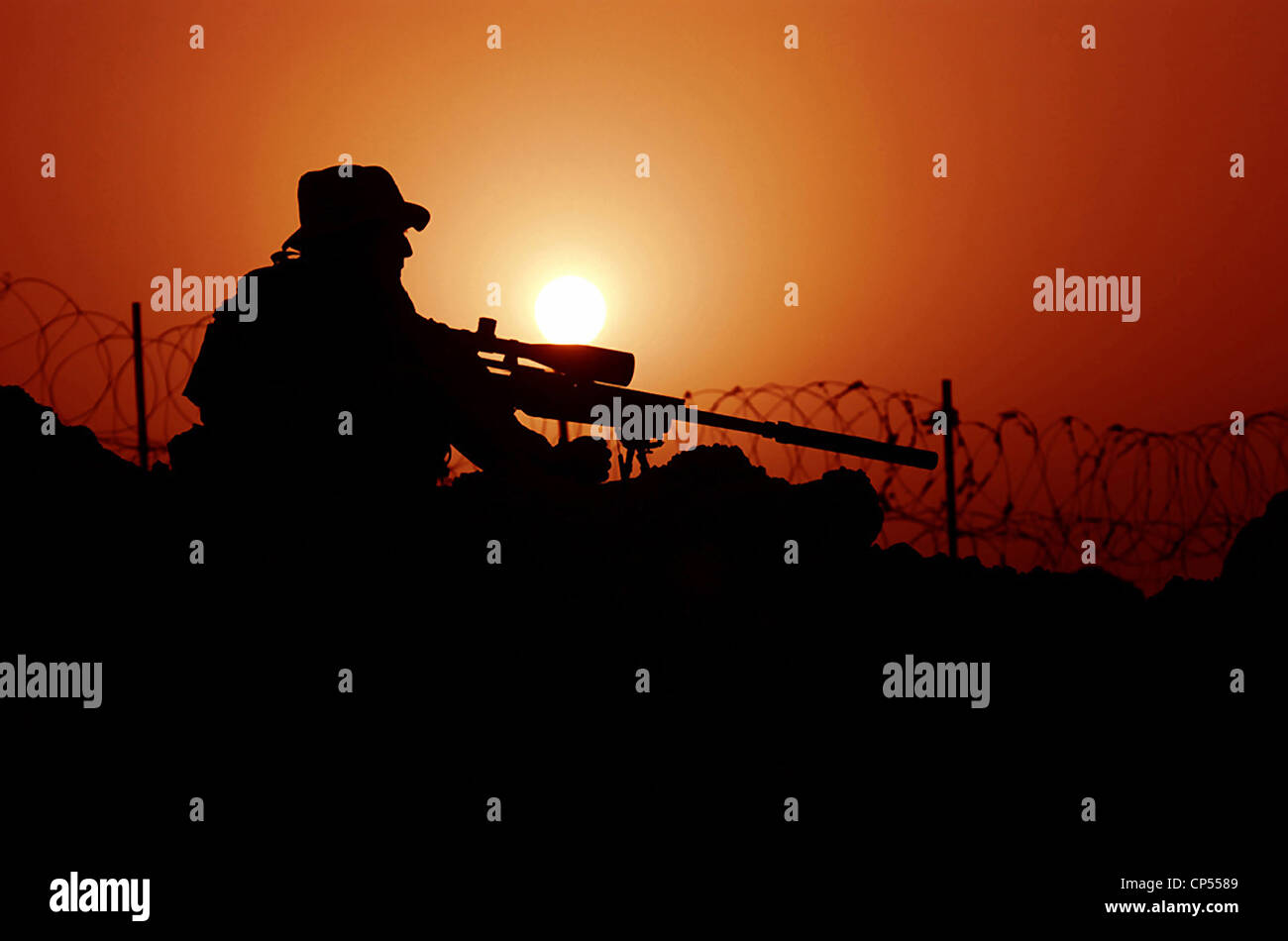 A US Special Forces soldier looks through his MK 12 sniper rifle at sunset September 7, 2007 in Rawah, Iraq. - Stock Image