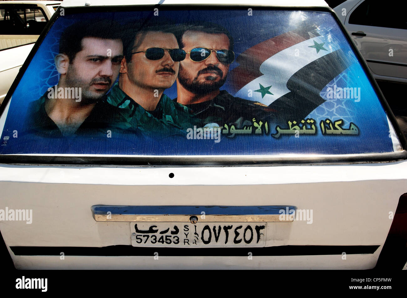 Syria - Bosra. Rear window of car depicted with images of men in uniform - Stock Image