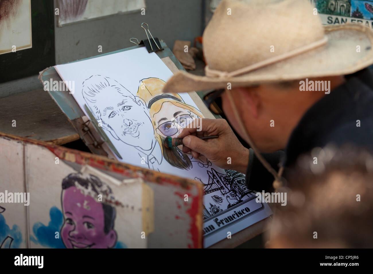 Street caricature artist drawing a couple portrait - San Francisco, California USA - Stock Image