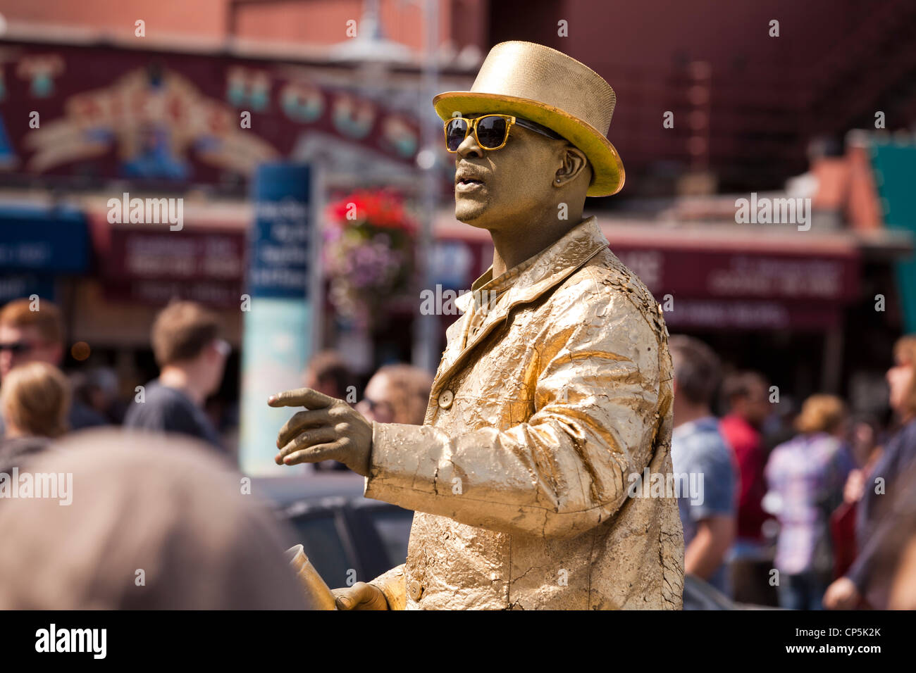 Gold man street performer on busy street - San Francisco, California USA - Stock Image