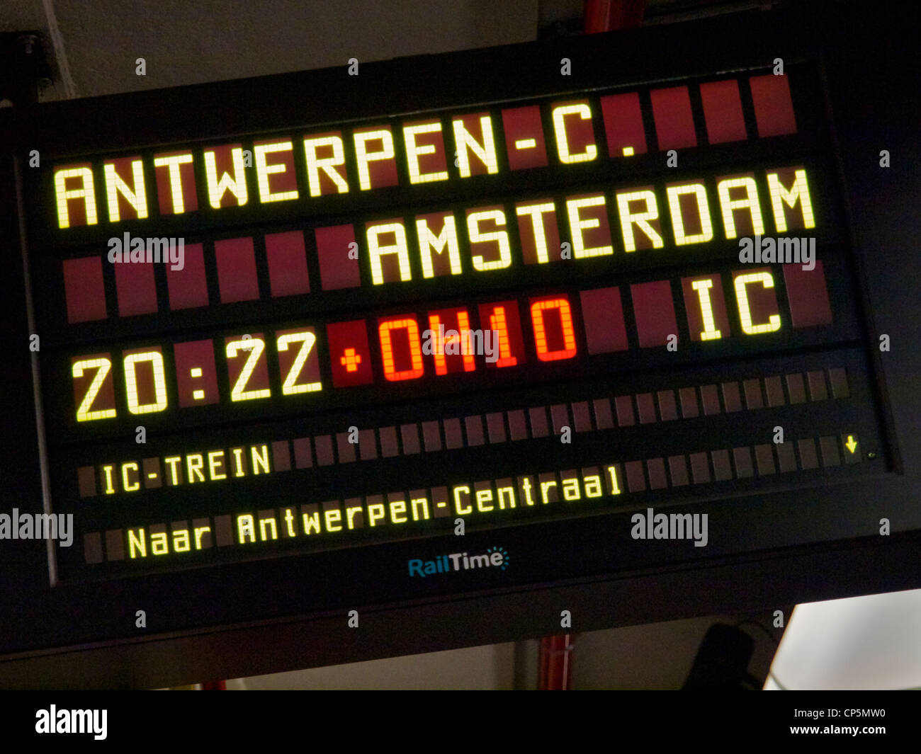 Modern digital sign saying the IC train from Brussels to Antwerp and Amsterdam is delayed by 10 minutes. - Stock Image