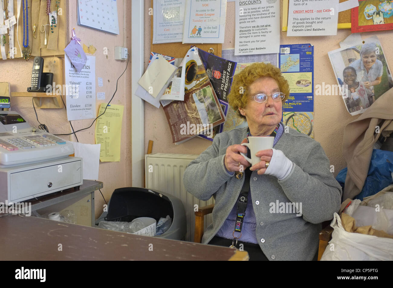 A helper in the Salvation Army charity shop in Falmouth, Cornwall - Stock Image
