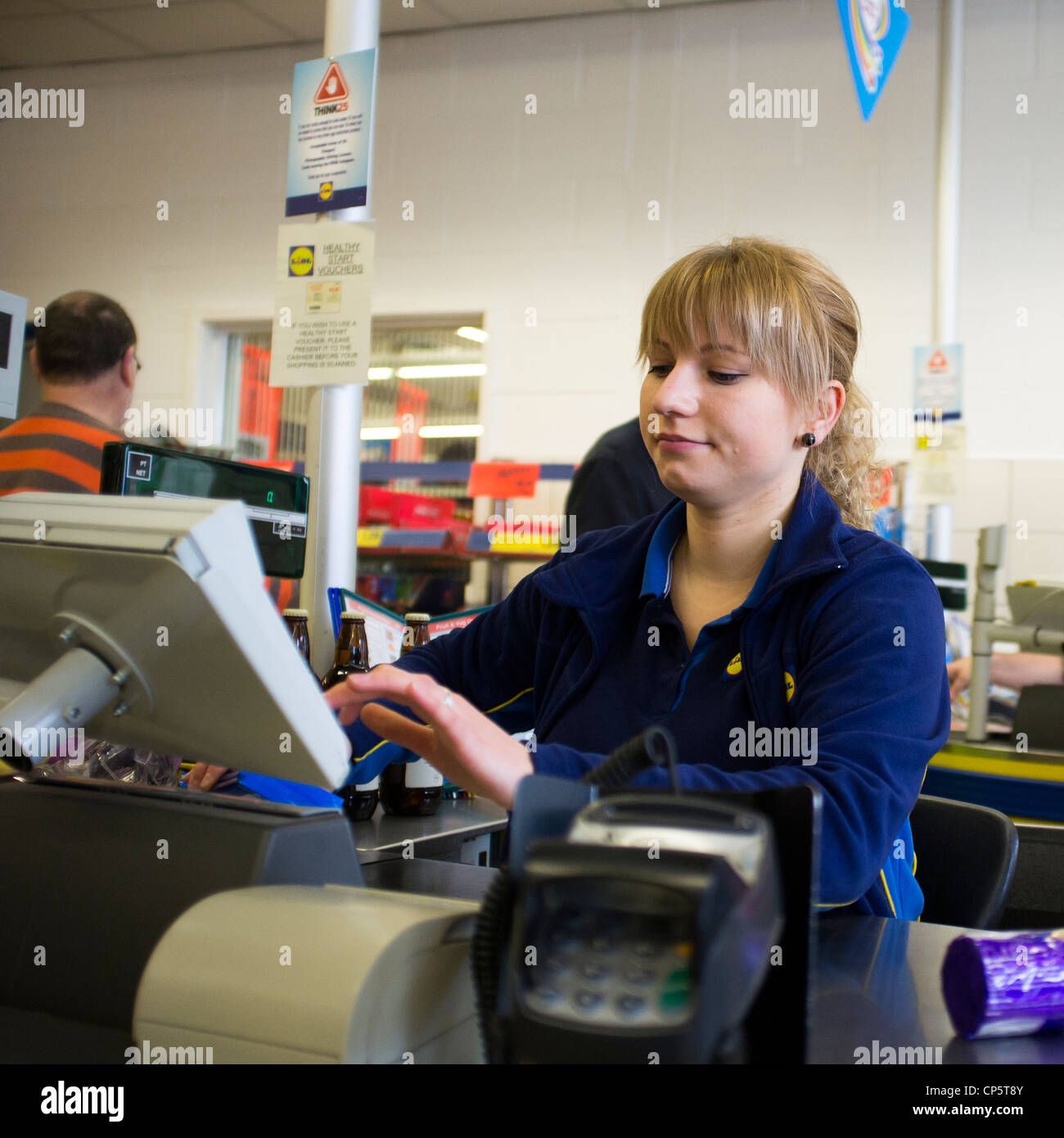 a young woman working at a Lidl supermarket checkout, UK - Stock Image
