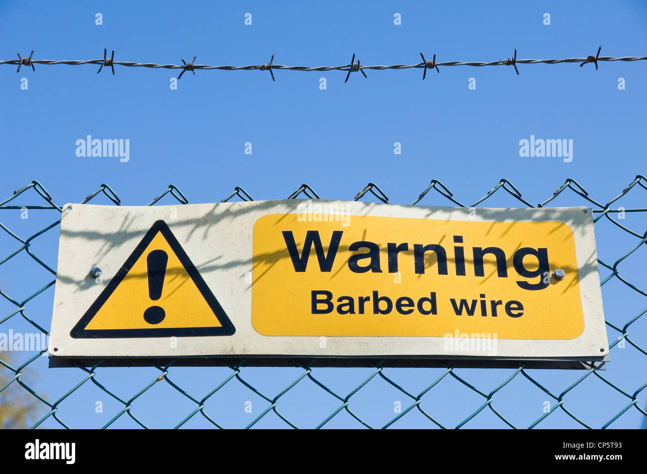 Warning sign on a barbed wire fence - Stock Image