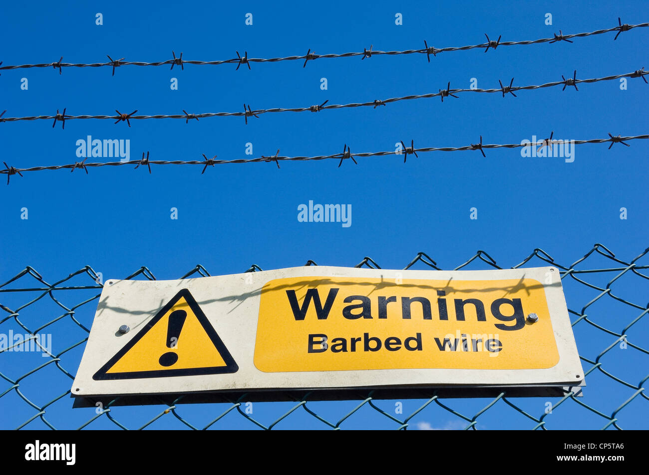 Warning sign on a barbed wire fence against bright blue sky - Stock Image