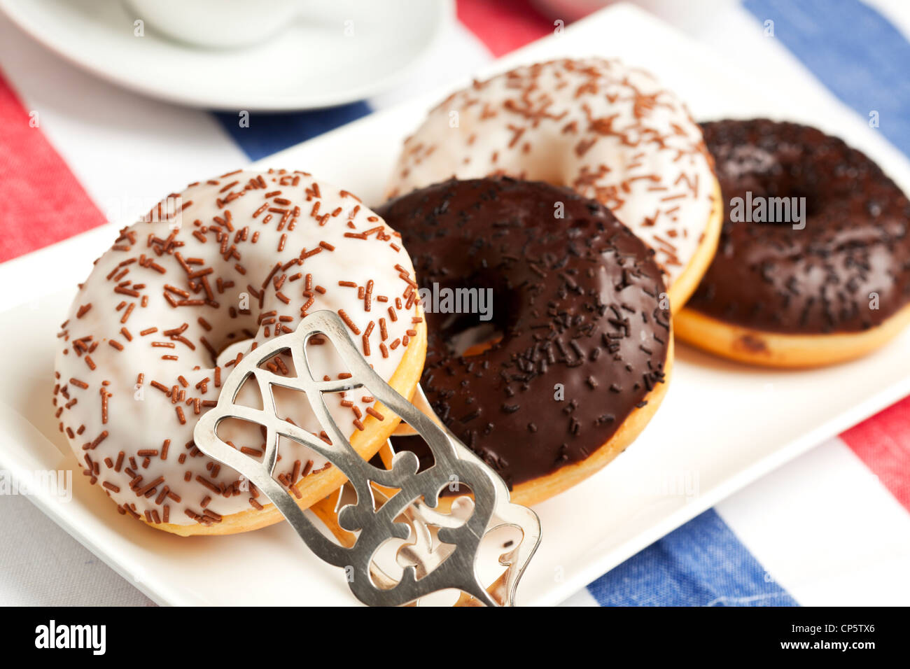 Donuts with dark and white chocolate icing and sprinkles on serving plate with pastry tongs - Stock Image