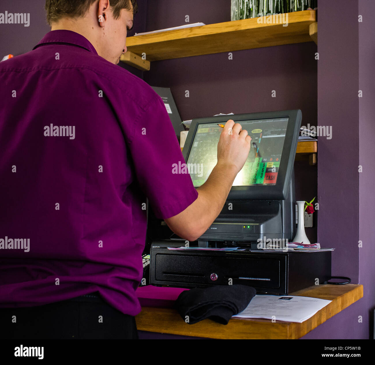a young worker using a touch screen till to enter details of a meal in a cafe resaturant, UK - Stock Image