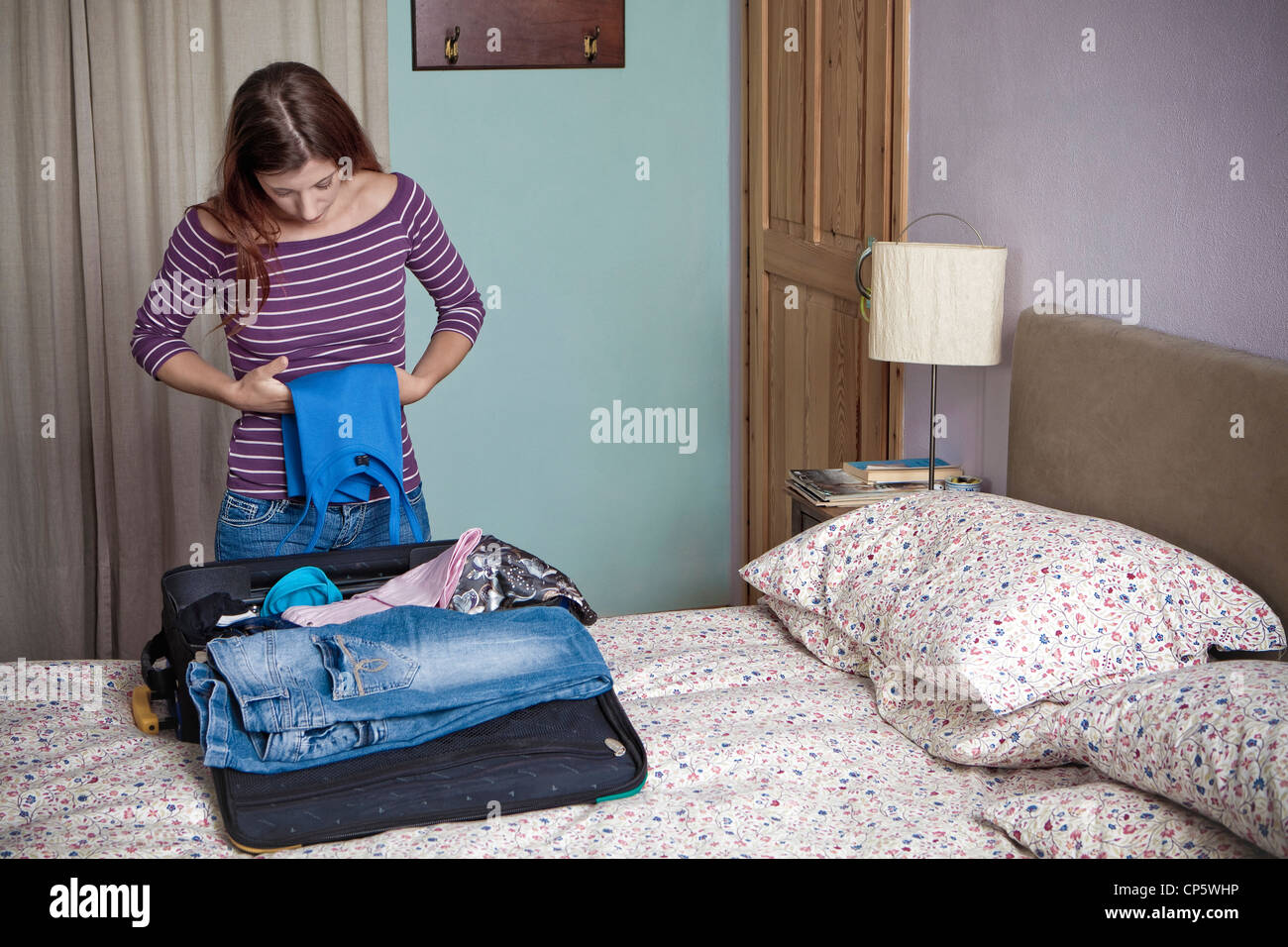 woman folds the clothes,suitcase - Stock Image