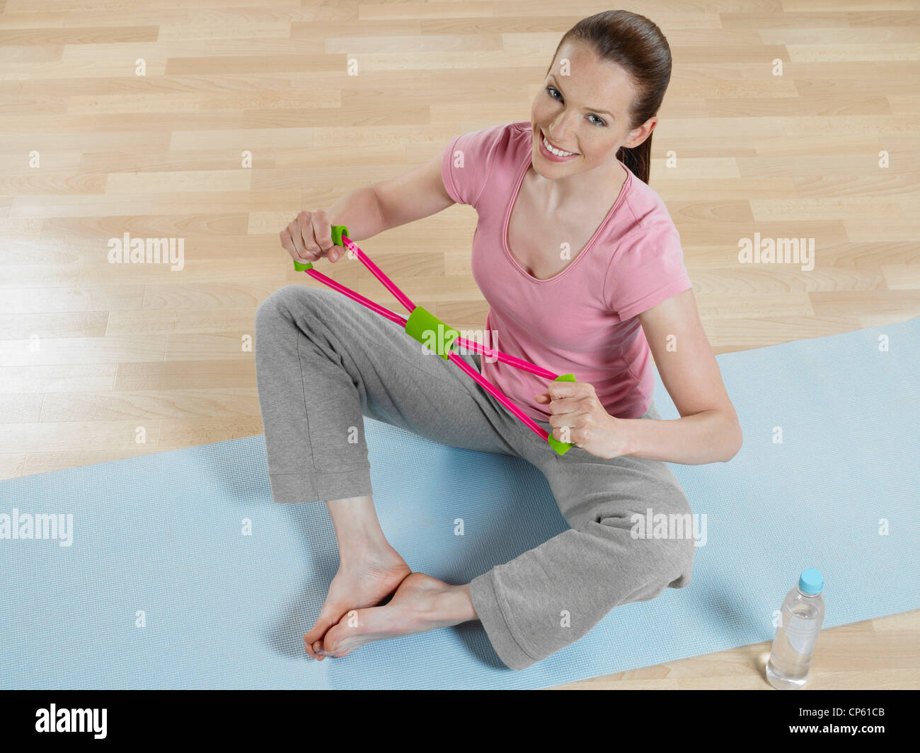 Young woman doing exercise, smiling, portrait - Stock Image