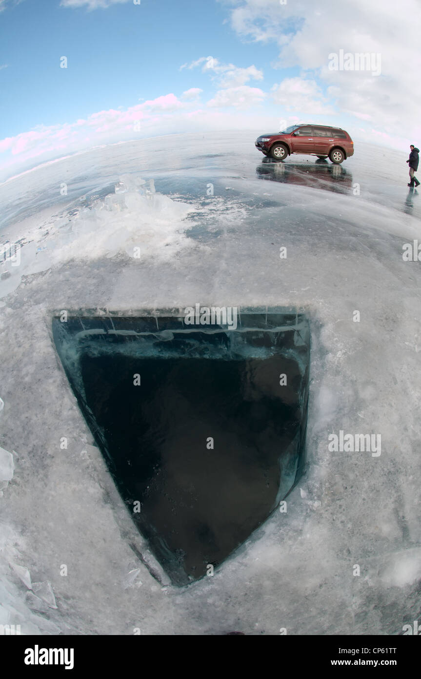 Car on frozen lake near diving ice-hole, island Olkhon, Lake