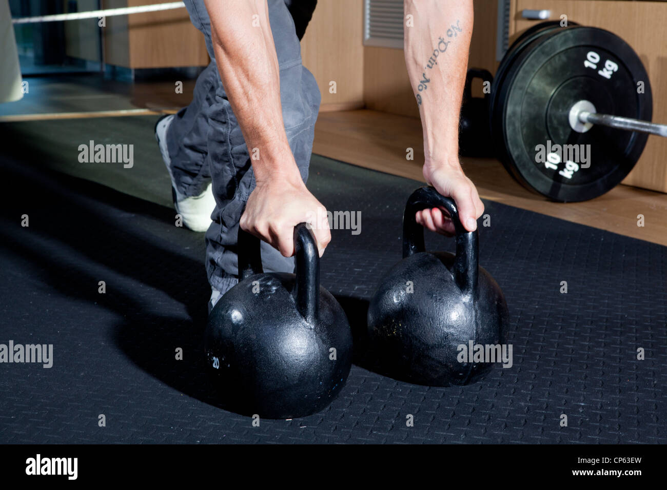 Tattooed arms lifting kettlebells at the gym during a crossfit session - Stock Image