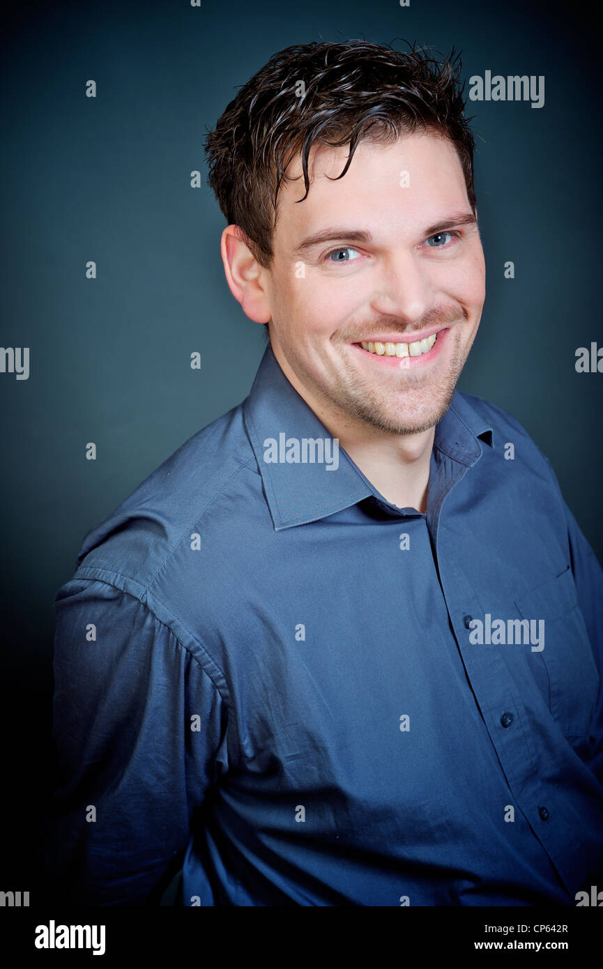 man with dark short hair, smiling , studioshot, blue background and blue - Stock Image