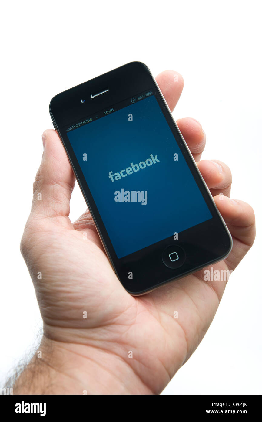Hand holding iPhone with Facebook logo - Stock Image