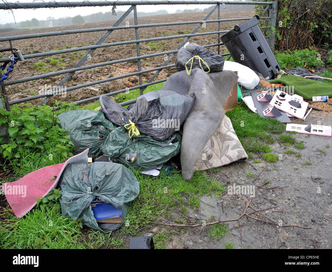 Fly tipping tip in gateway in UK countryside - Stock Image