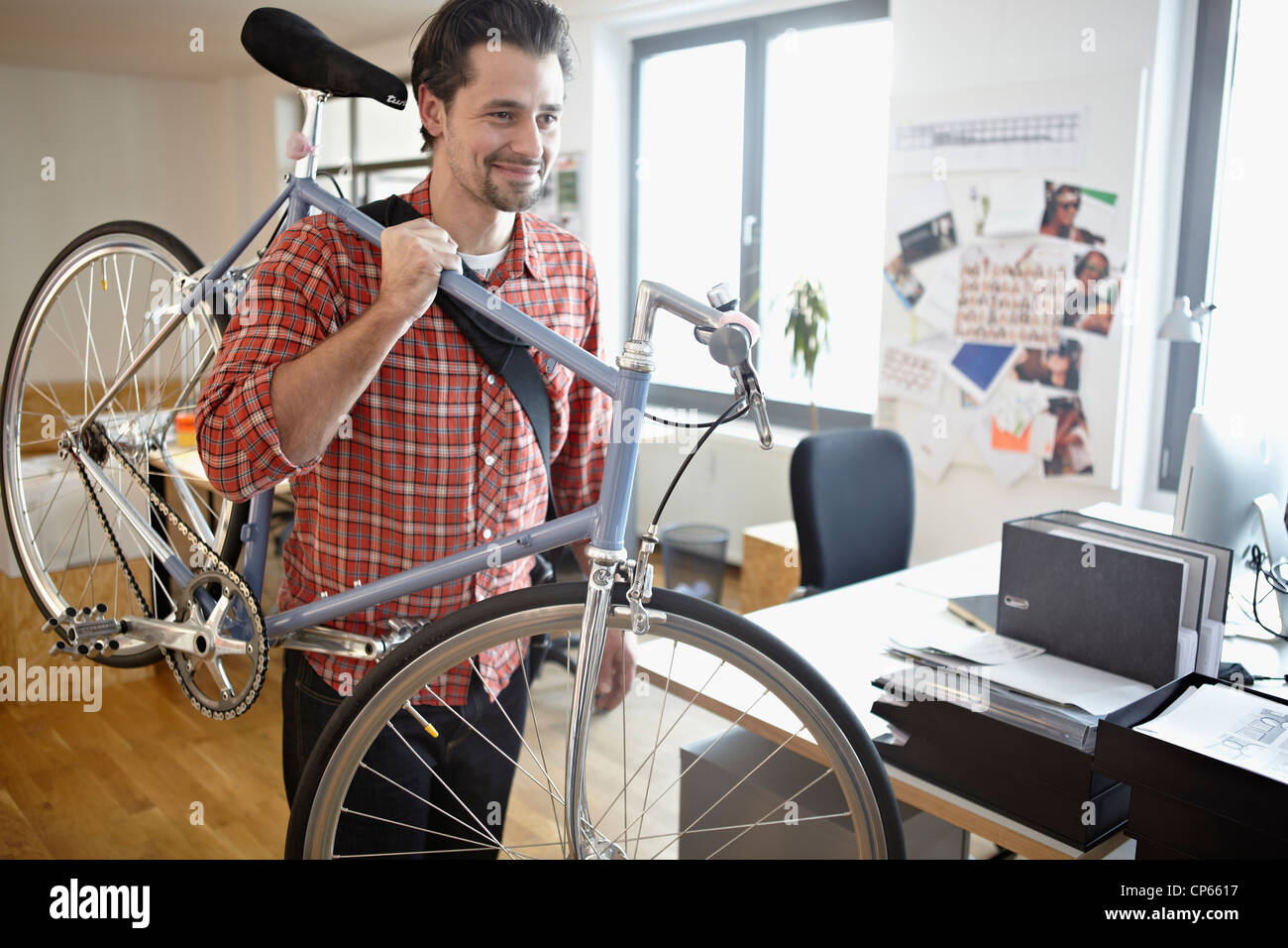 Germany, Cologne, Mid adult man carrying bicycle, smiling - Stock Image