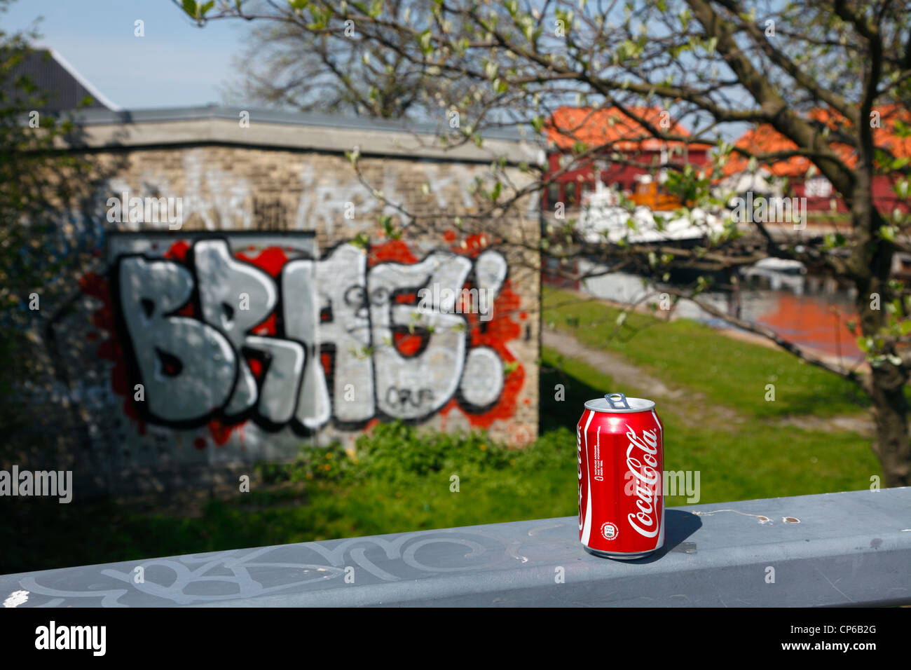 Red Coca Cola can standing on a grey handrail in background a canal, blooming tree, and BRAG! as graffiti on a sunny - Stock Image
