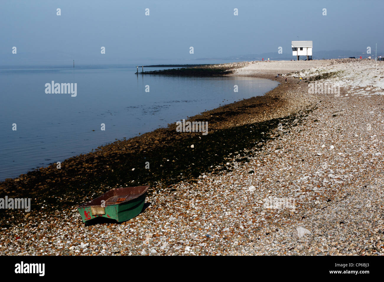 Small green dinghy on the shingle shore at Morecambe, Lancashire. - Stock Image