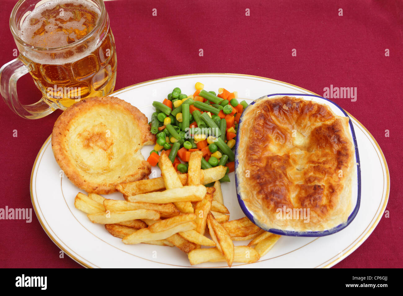 A pub grub style meal of a meat pie served with mixed veg, chips, Yorkshire pudding and a glass of lager. - Stock Image