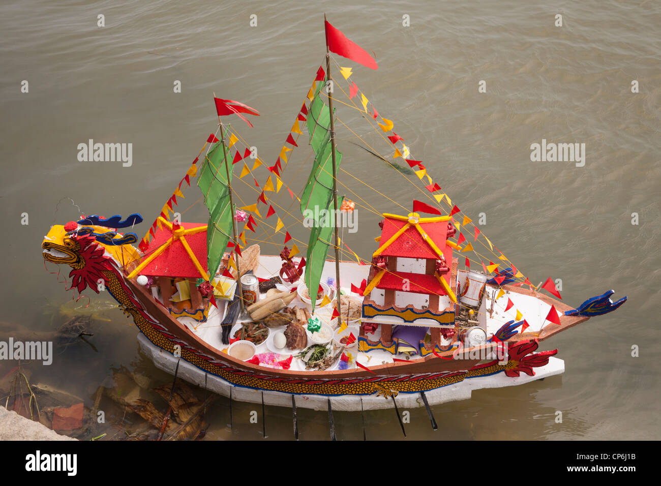 A replica miniature model boat, laden with religious offerings to the Sea Goddess, on Thu Bon River, Hoi An, Vietnam Stock Photo