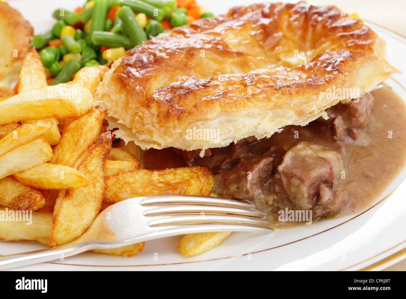 A meal of a homemade steak and kidney pie with french fried potato chips and mixed vegetables - Stock Image
