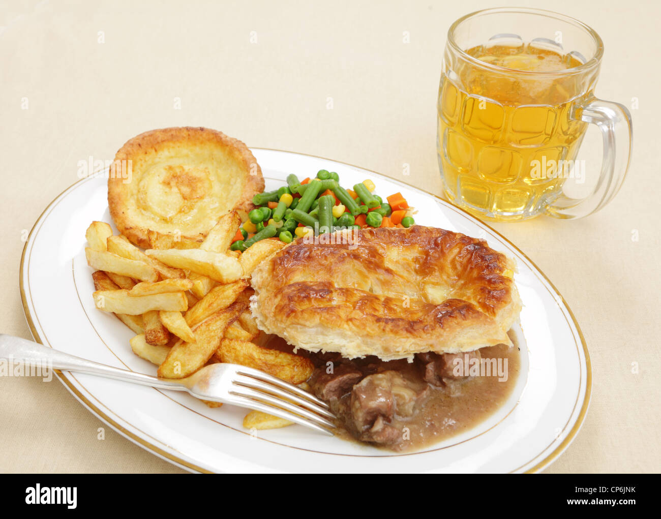 A  homemade steak and kidney pie with french fries yorkshire pudding and mixed vegetables served with a pint of - Stock Image