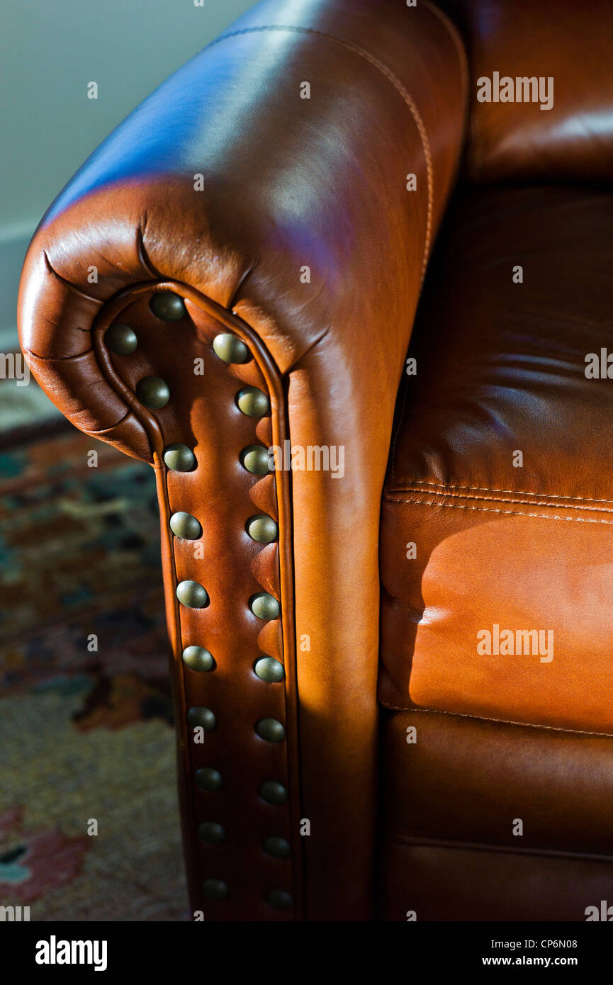Close up photograph of sunlight on a fine leather recliner seat - Stock Image