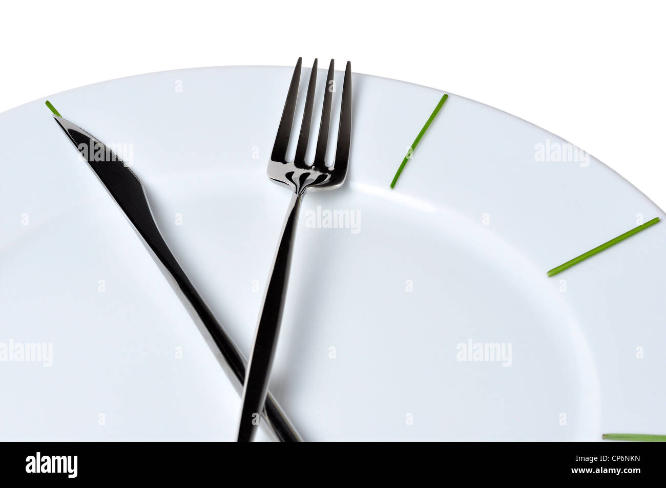 Clock made of knife and fork, isolated on white background - Stock Image