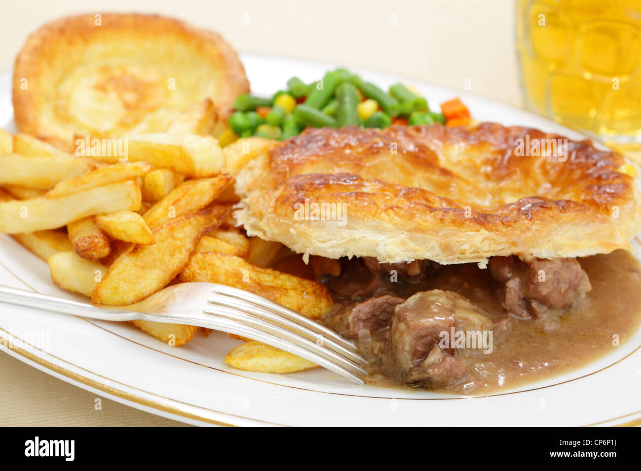 A meal of a homemade steak and kidney pie with french fried potato chips yorkshire pudding and mixed vegetables - Stock Image