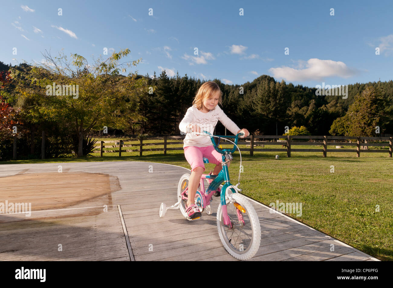 Girl riding here bike on wooden decking, New Zealand - Stock Image