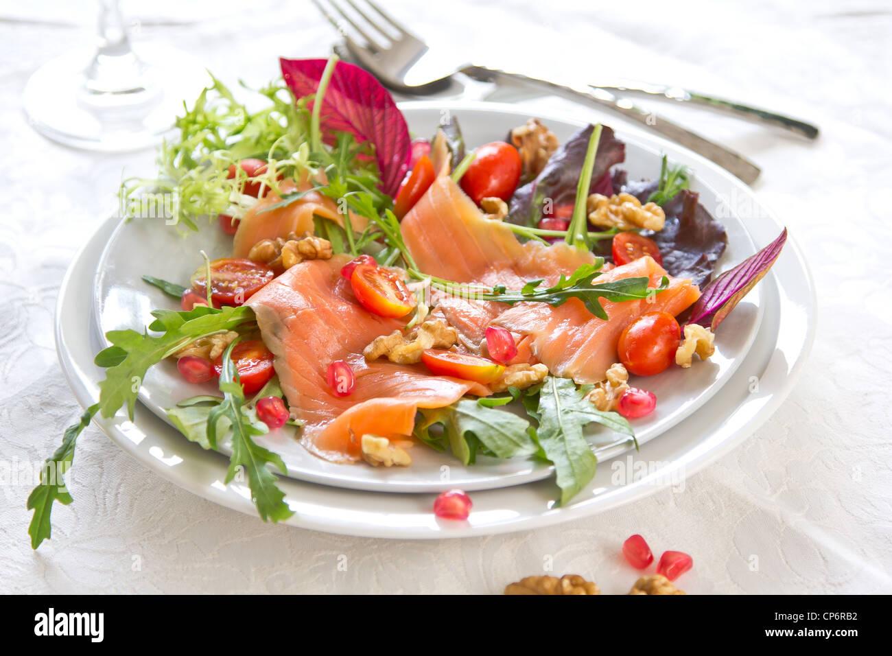 Smoked salmon with pomegranate and walnut salad - Stock Image