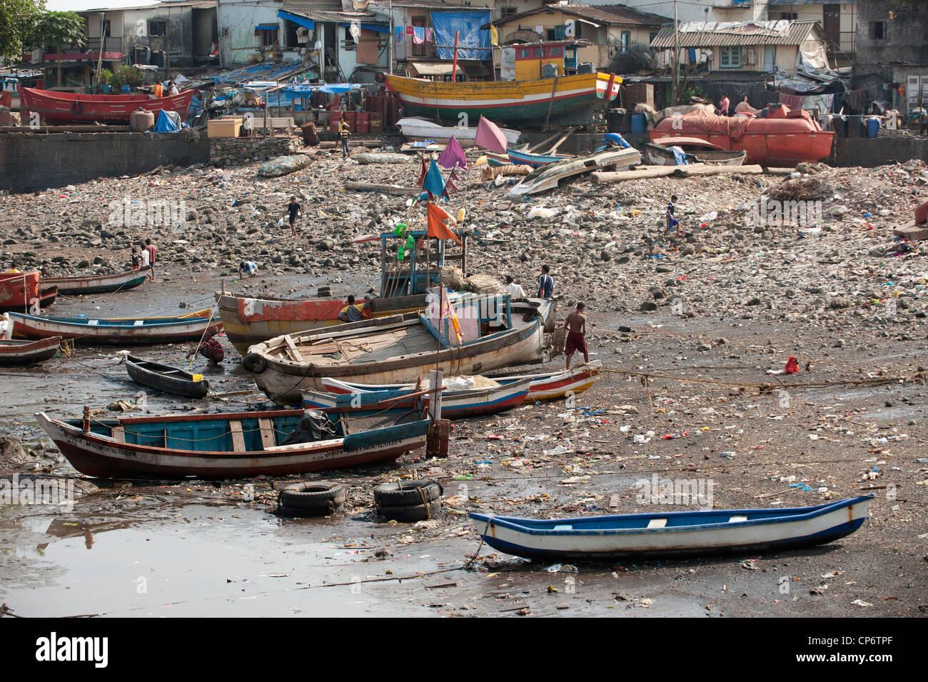 Fishermen and children on a dirty fishing harbor beach in Mumbai. Stock Photo